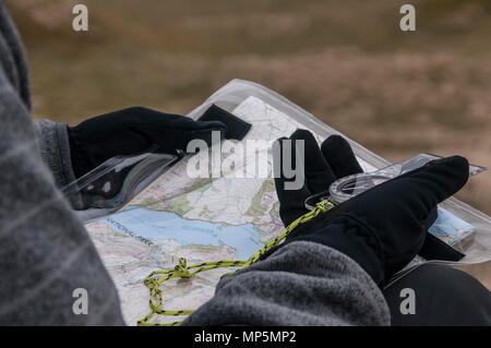 Walker using a compass and map to find way - Stock Image