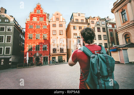 Man tourist sightseeing Stockholm city Gamla Stan landmarks traveling lifestyle girl taking photo by smartphone Europe trip summer vacations - Stock Image