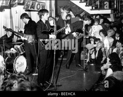 The Beatles (L-R) Ringo Starr, Paul McCartney, George Harrison, and John Lennon perform in a small club in 1962. - Stock Image