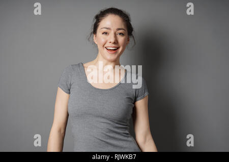 happy young woman with bright face and radiant smile - Stock Image