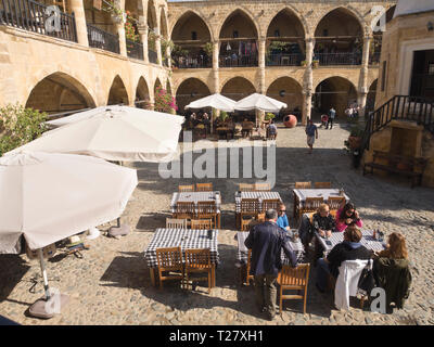 The Büyük Han in the turkish part of Nicosia Cyprus, a historic building with shops and restaurants attracts sightseers and locals - Stock Image