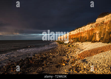 Hunstanton Cliffs at sunset with dark stormy sky, on Norfolk coast, where white chalk overlays red limestone in a colourful formation. England, UK. - Stock Image