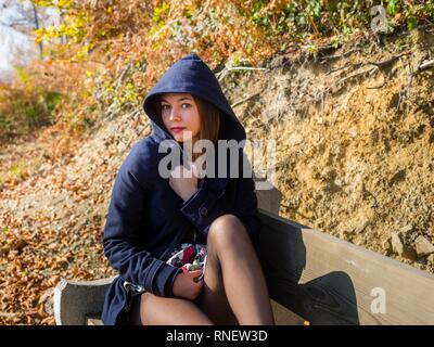 Beautiful teenager girl wearing hooded jacket serious looking at camera - Stock Image
