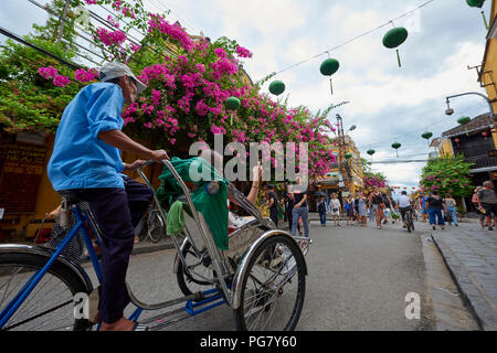 Bicycle tour guides in the UNESCO protected town of Hoi An, Vietnam. From early afternoon, all motorised traffic is prohibited inside the historical t - Stock Image