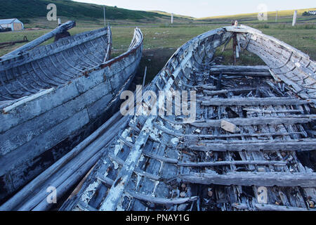 A view of the inside of the broken battered hull of a boat pulled up on the beach showing the hull's shape and form - Stock Image