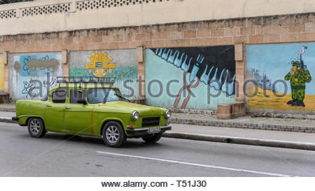 Old obsolete classic vintage car driving in front of caricatures themed on 'peace' or 'no war' - Stock Image