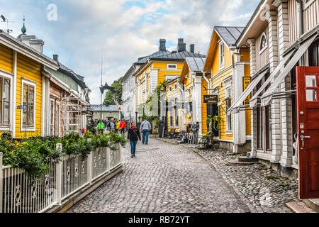 Tourists and local Finns walk past shops along the cobbled streets of the medieval old town section of Porvoo, Finland. - Stock Image