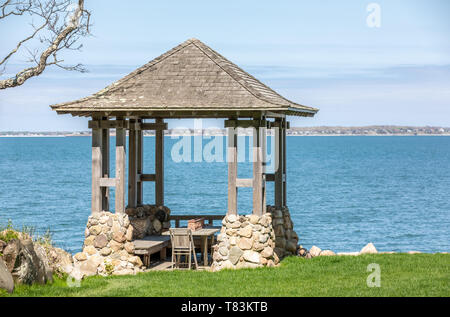 small wood and stone gazebo with bay beyond - Stock Image