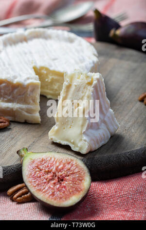 French soft Camembert cheese, original Camembert de Normandie served with fresh ripe figs and grapes, close up - Stock Image