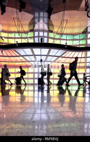 Air passengers, people walking, neon lights art installation by Michael Hayden, pedestrian tunnel, Chicago O'Hare International Airport Terminal, USA - Stock Image