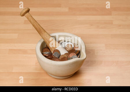 A pestle and mortar filled with UK pound sterling coins - Stock Image