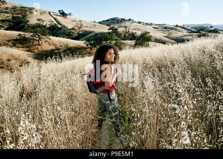 Young woman with curly brown hair hiking in urban park. - Stock Image