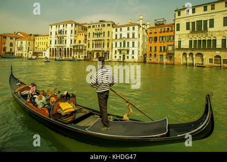 Tourists enjoy a gondola ride on the Grand Canal in Venice, Italy - Stock Image