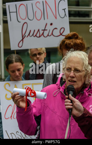 London, UK. 17th October 2018. Ruth London from Fuel Poverty Action hold up a copy of the open letter they are about to deliver at the  protest outside the Ministry of Housing, Communities and Local Government by residents living in tower blocks covered in Grenfell-style cladding, Fuel Poverty Action, and Grenfell campaigners demanding that the government make all tower-block homes safe and warm. Credit: Peter Marshall/Alamy Live News - Stock Image