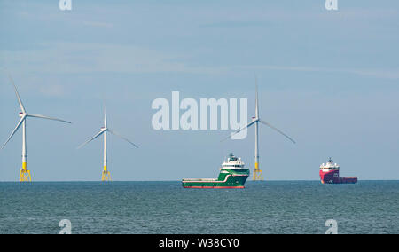 Offshore supply ships anchored by wind turbines in offshore windfarm, North Sea, Aberdeen, Scotland, UK - Stock Image
