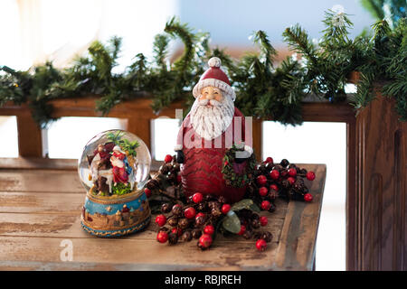 Christmas decorations, a snow globe with nativity scene and Santa Clause on a wooden table with garland on a railing. - Stock Image
