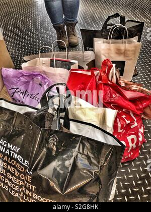 Retail therapy! Woman surrounded by bags of shopping. - Stock Image
