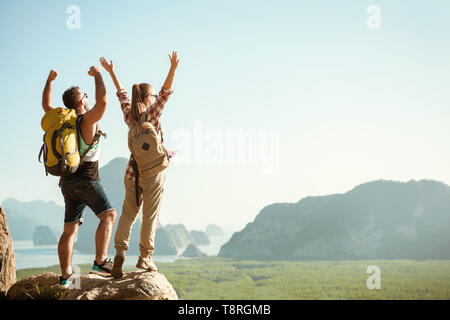 Two happy tourists stands with raised arms on viewpoint - Stock Image