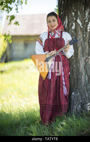 Young attractive woman in traditional russian clothes standing under a tree with the balalaika and posing for a photo - vertical shot - Stock Image