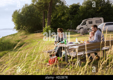 Parents with sons (18-23, 0-1 months) sitting by picnic table - Stock Image