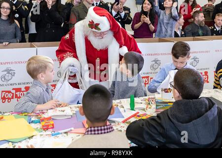 Santa Claus greets children during a Toys for Tots Christmas Event at Joint Base Anacostia-Bolling December 11, 2018 in Washington, DC. Toys for Tots is a Marine Corps Program that collects new unwrapped toys and distribute those toys to less fortunate children at Christmas. - Stock Image