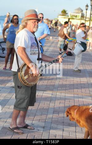 Male musician street performer playing banjo for crowds of tourists at Mallory Square on Key West, Florida Keys, Florida, USA - Stock Image