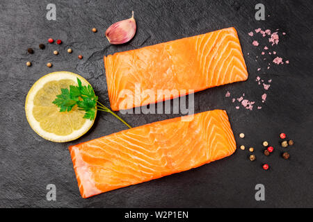 Two slices of raw salmon with parsley, salt, pepper, garlic and lemon on black - Stock Image