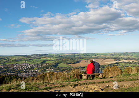 Couple sitting on bench, on the Chevin, enjoying the view over Otley and Lower Wharfedale, West Yorkshire, England UK - Stock Image