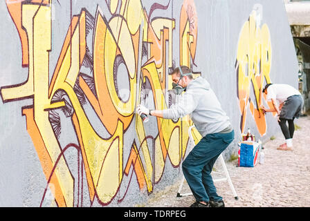 Graffiti artists painting colorful mural on a grey wall - Creative men performing drawing murals - Stock Image