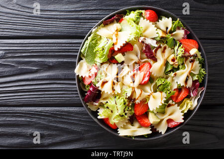 Delicious Italian pasta salad with avocado, strawberries, lettuce, dressed with balsamic sauce close-up on a plate on the table. horizontal top view f - Stock Image