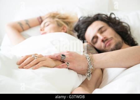 A cool young couple relaxing in bed with their eyes shut. - Stock Image