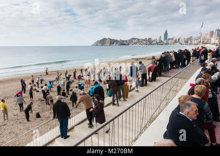 Seniors keeping fit on the beach in Benidorm, Spain. Men women oap's, elderly fitness class spectators watching - Stock Image