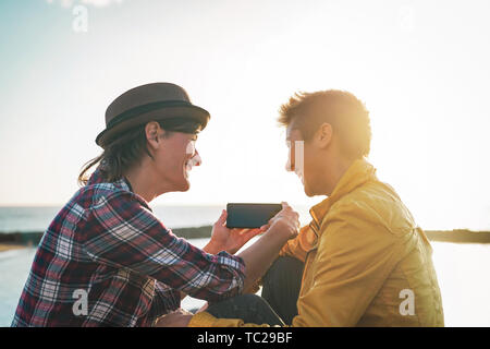 Happy lesbian couple watching on mobile phone next the beach at sunset - Young homosexual women having fun with new trends technology - Stock Image