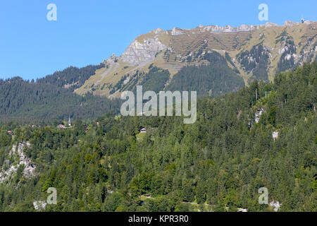 Rocky peaks and wooded slopes and smaller hills as seen from Lauterbrunnen - Stock Image