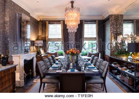 Lit chandelier over set table - Stock Image