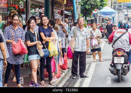 Bangkok, Thailand - 1st August 2017 -  People waiting for a bus in Chinatown.  This one of the busiest areas of the city. - Stock Image