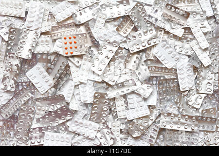 Orange pills in blister pack in front of many empty packages, drug overdose concept background - Stock Image