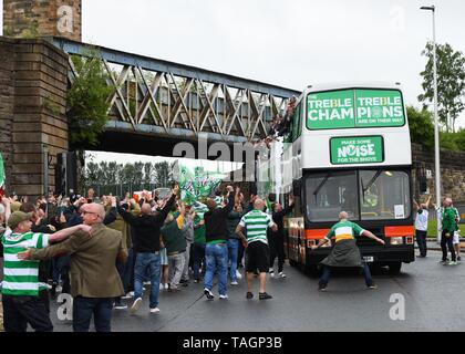 25th May, 2019. Glasgow, Scotland, UK, Europe. Scottish Cup winners, Celtic Football Club fans celebrate their teams achievement of three consecutive seasons winning all domestic trophies. The first time a domestic club has completed the triple treble in world football. Pictured are the players and staff aboard open top buses surrounded by exuberant fans - Stock Image