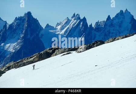 The figure of a lone climber in the French Alps with the Chamonix Aiguilles beyond - Stock Image