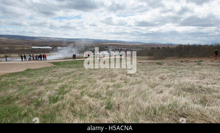 Tourists looking at hot springs zt Geysire, South Iceland - Stock Image