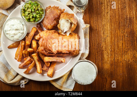Traditional fish in beer batter and chips with green pea and tartar sauce.Top view - Stock Image