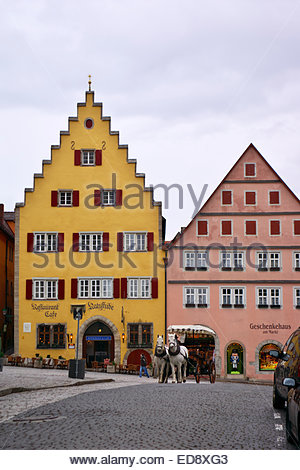 A coachman drives his wagon in the Marktplatz square in Rothenburg ob der Tauber, ready to take tourists for rides - Stock Image