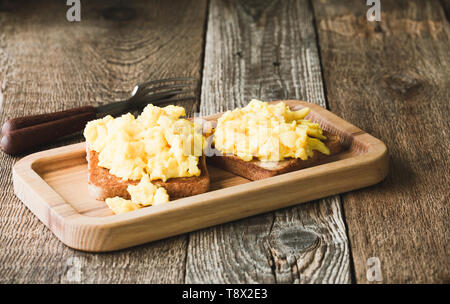 Scrambled eggs on toasted bread, breakfast time, close up, selective focus - Stock Image