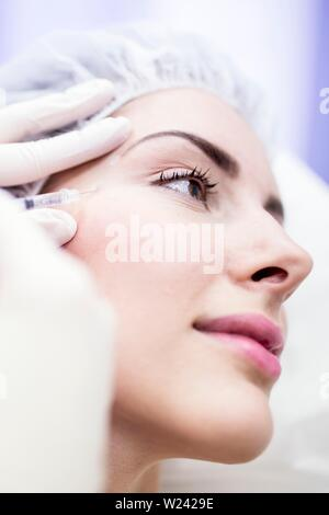 Beauty technician injecting botox into woman's face. Botox is used medically to treat certain muscular conditions and cosmetically to reduce wrinkles. - Stock Image