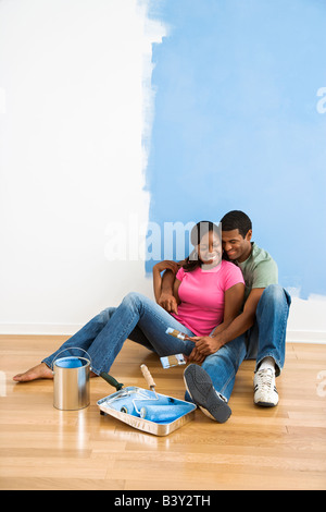 African American couple sitting together relaxing next to half painted wall and painting supplies - Stock Image