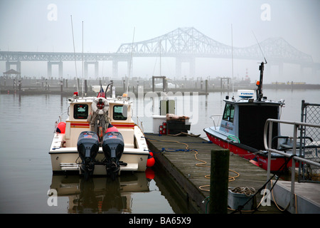 Boat docked in marina on the Hudson River, foggy Tappan Zee Bridge in the background, Tarrytown, NY, USA - Stock Image