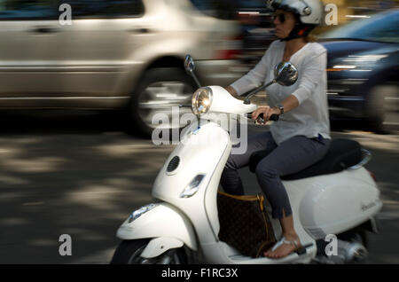 Women on a white moped in France (motion blurred, panned) - Stock Image