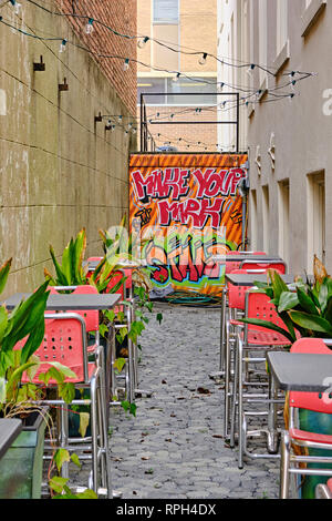 Empty outdoor restaurant courtyard for a bar or outdoor dining with a brightly painted wall and high top tables in Montgomery Alabama, USA. - Stock Image