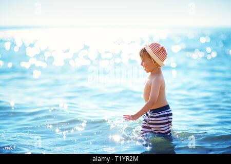 Boy walking at sea in straw hat - Stock Image