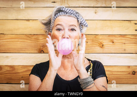 Funny and alternative old people caucasian beautiful woman with pink bubble chewing gum - portrait of youth active senior lady having fun - no limit a - Stock Image